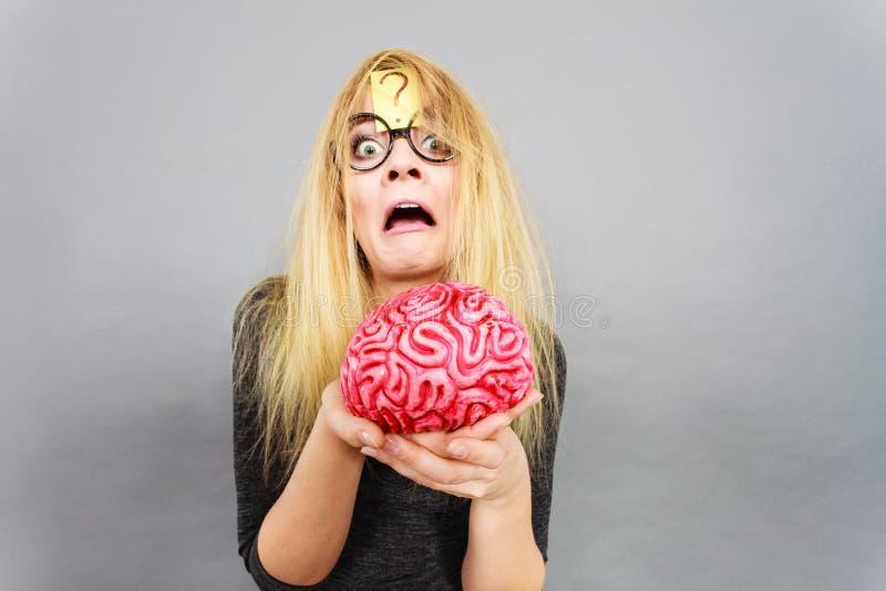 Sonderbare Frau, die das Gehirn hat Idee hält lizenzfreies stockbild