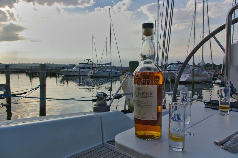 Sonderborg, Dinamarca - 30 de junho de 2012 - garrafa do uísque escocês do único malte de Talisker com vidros na tabela na cabina imagens de stock royalty free
