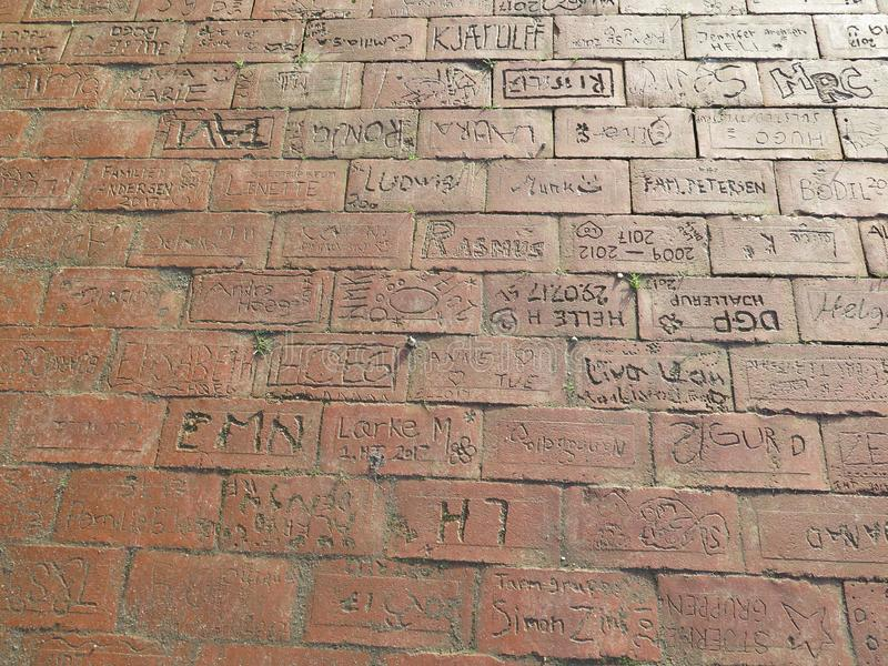 Signed inscribed bricks in pavement at Scouts hut in Sothern Denmark. Sonderburg - Denmark, January 1, 2019: Individually signed bricks in pavement at Scouts hut stock images