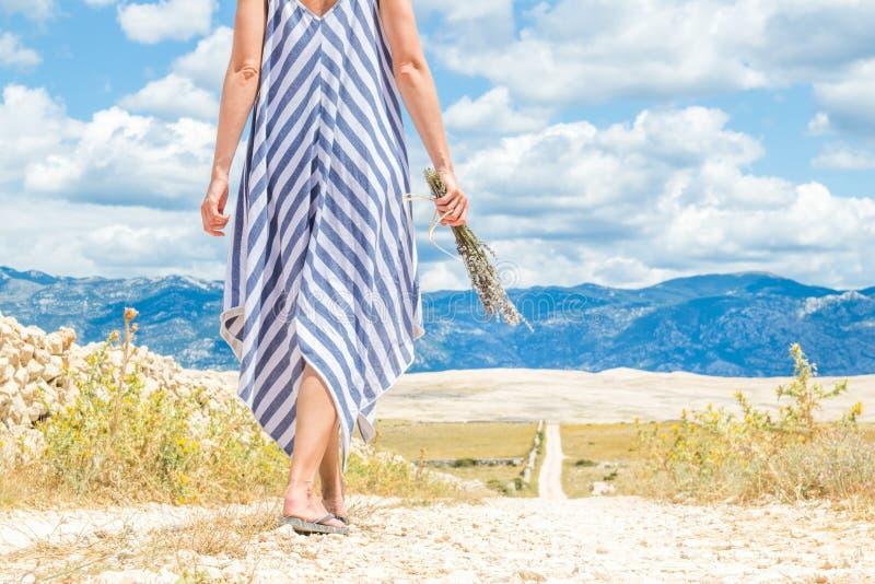 Sonderkommando der Frau im Sommerkleiderholdingblumenstrauß von Lavendelblumen beim Gehen im Freien durch trockenes felsiges lizenzfreie stockbilder