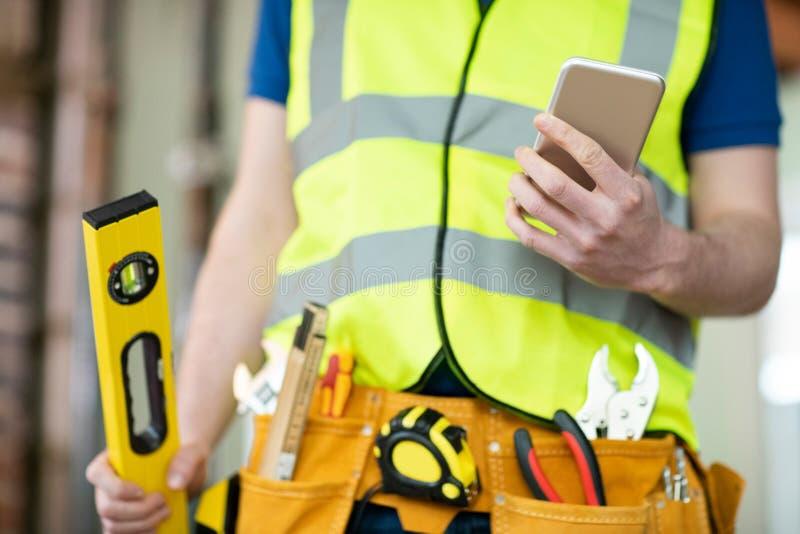 Sonderkommando des Bauarbeiters auf Baustelle-tragendem Werkzeug-Gurt unter Verwendung des Handys stockbilder