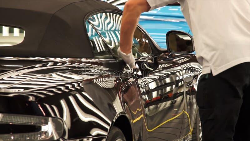 Sonderkommando eines Mannes, der ein Auto poliert lizenzfreie stockfotos