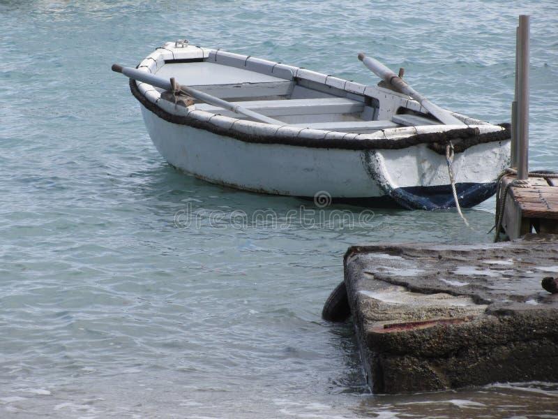 Sondern Sie das hölzerne Ruderboot aus, das in einem Hafen auf dem Meer festgemacht wird Toskana, Italien stockfoto