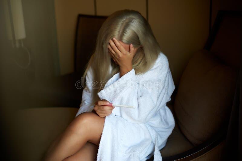 Sondern Sie die traurige Frau aus, die einen Schwangerschaftstest halten sich beschwert, der, zu Hause auf einer Couch im Wohnzim lizenzfreie stockfotografie