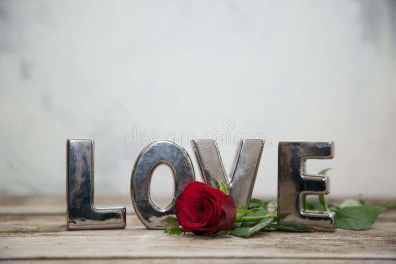 Sondern Sie Rosafarbenes auf hölzerner Tabelle mit der Liebe aus, die formuliert wird stockbilder