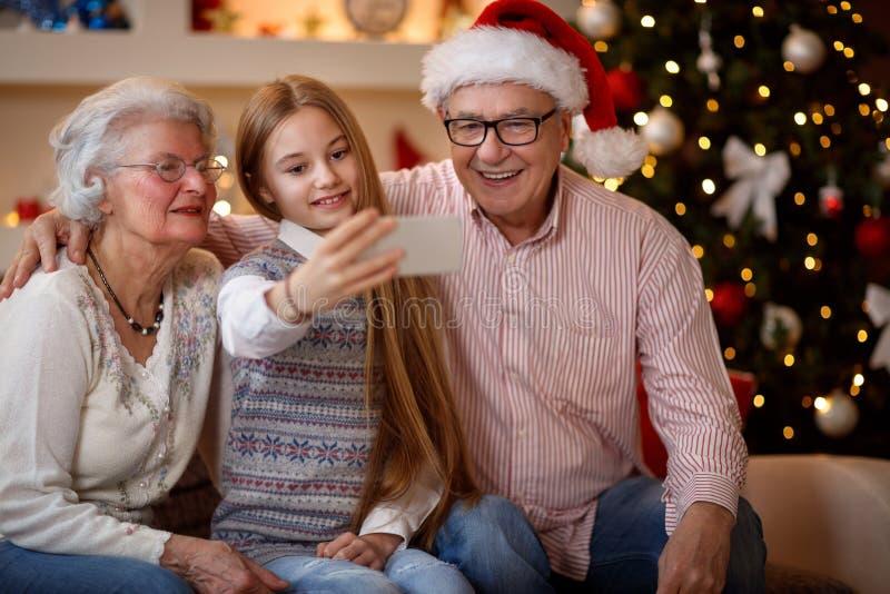 """Sondotter för lycklig familjögonblicks†som """"tar selfie med smartp royaltyfri fotografi"""