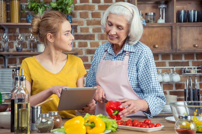 Sondotter och farmor som tillsammans lagar mat arkivbilder
