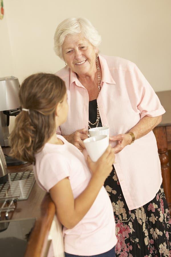 Sondotter som delar kopp te med farmodern i kök royaltyfria bilder