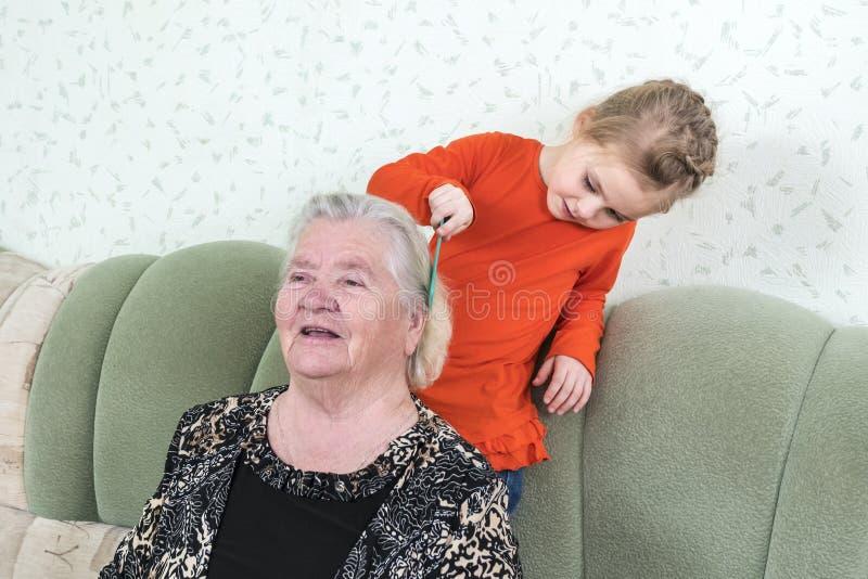 Sondotter som kammar hennes farmor arkivfoto