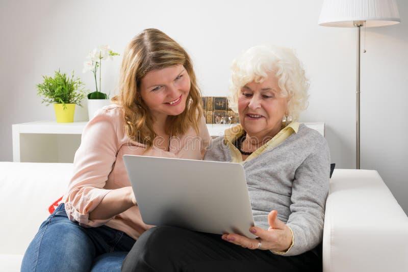 Sondotterundervisningmormor hur man använder datoren arkivbild