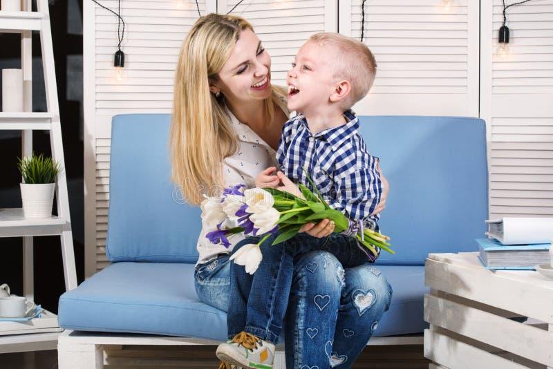 Sonen gratulerar hans älskade moder och ger henne en bukett av tulpan Begreppet av berömmen, dag för kvinna` s dagmamma s arkivfoto