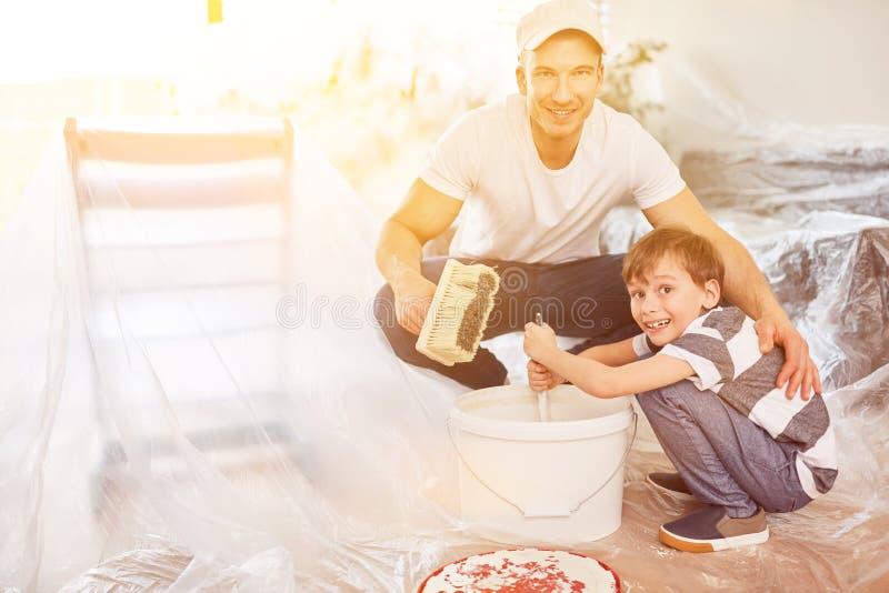 Sonen hjälper fadern med hem- renovering arkivfoton