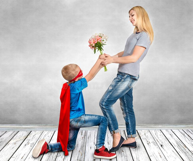 Sonen i dräkten av en superhero ger hans moder en bukett av blommor fotografering för bildbyråer