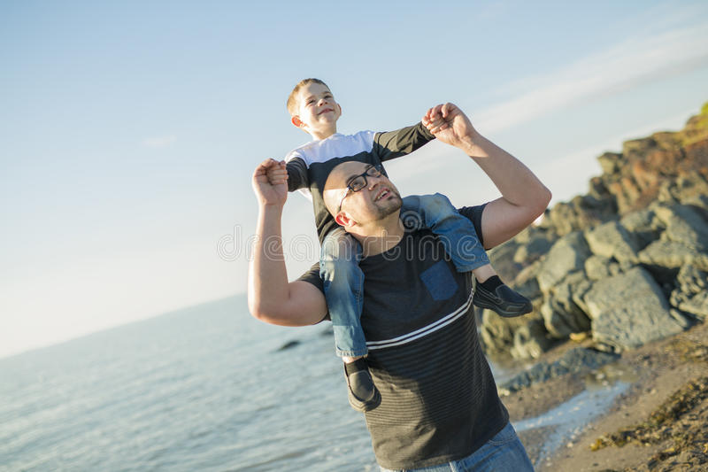 Sonen på fader knuffar på stranden som har rolig solnedgång tillsammans arkivfoto