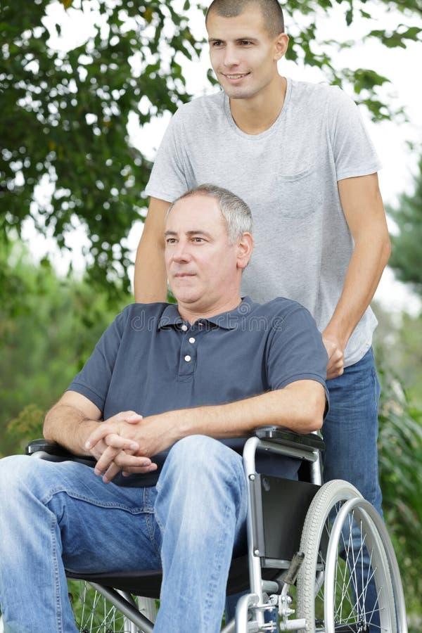 Sonen som går med den rörelsehindrade fadern i rullstol på, parkerar royaltyfria foton