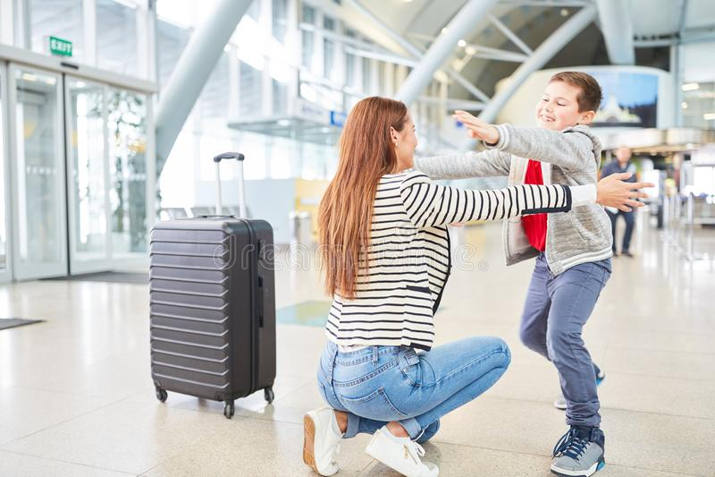 Sonen välkomnar hans moder i flygplatsterminalen royaltyfria foton