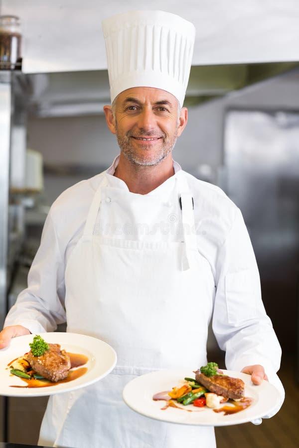 Sonfident男性厨师用熟食在厨房里 库存照片
