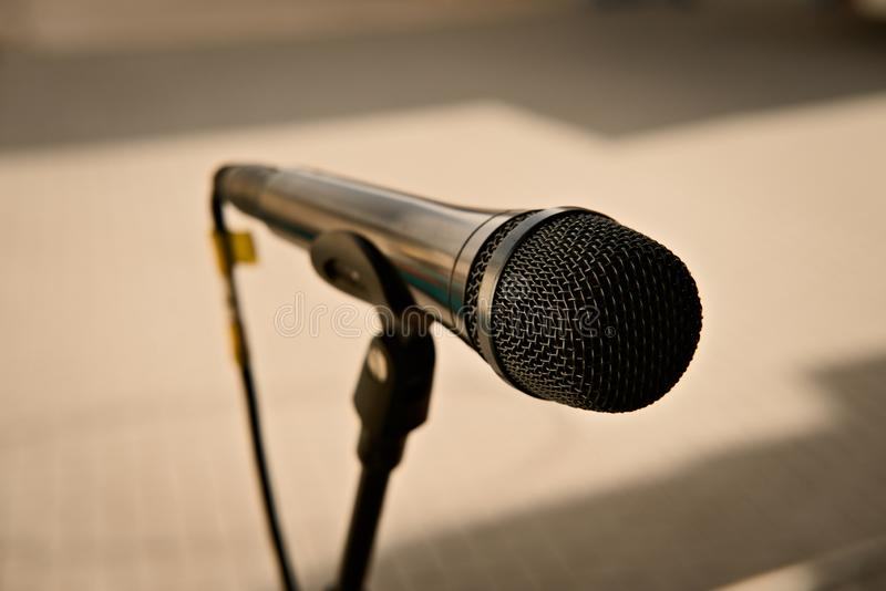 Microphone on a stand. Song, club, entertainment, audience, professional, sing, performance, disco, party, rays, stand, project, band, lights, music, karaoke stock photography
