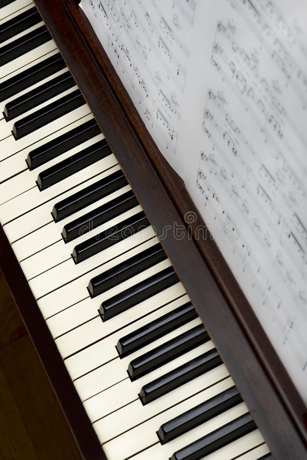 Song sheet music on wooden upright piano with white and black k royalty free stock photography