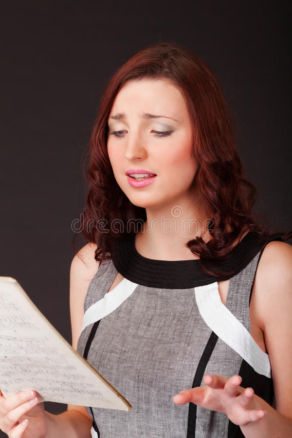 Song to you. Young girl with music sheet is singing some romantic song stock images