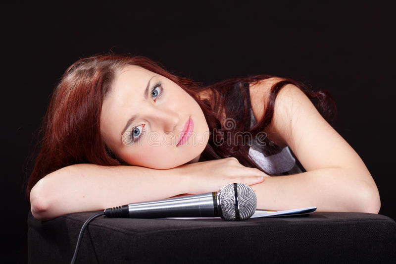 Song to you. Young girl with microphone is composing some romantic song royalty free stock photography