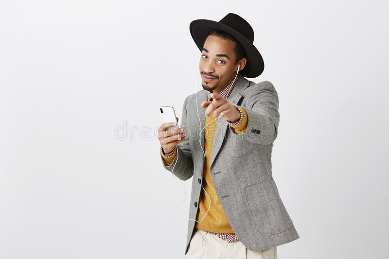 This song is about you. Portrait of charming dark-skinned stylish student in hat and trendy outfit holding smartphone royalty free stock photo