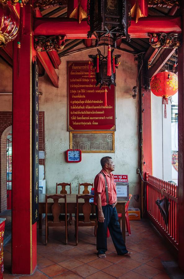 Songkhla, TAHILAND - Lokalny facet przy starym rocznika budynkiem Songkhla miasta filaru świątynia z Chińskimi lampionami przy Na fotografia royalty free