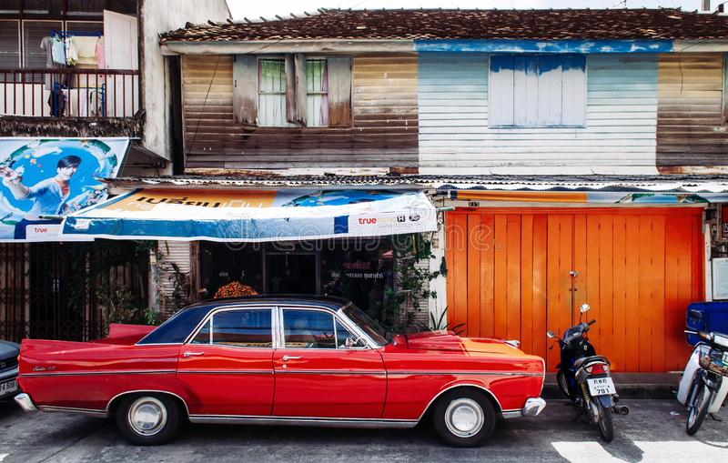Songkhla, TAHILAND - Vibrant vintage sport car and old local style wooden house in Songkhla old town. Nang Ngam royalty free stock images