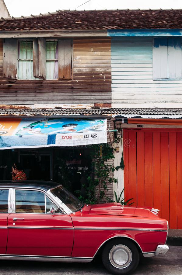 Songkhla, TAHILAND - Vibrant vintage sport car and old local style wooden house in Songkhla old town. Nang Ngam stock photography