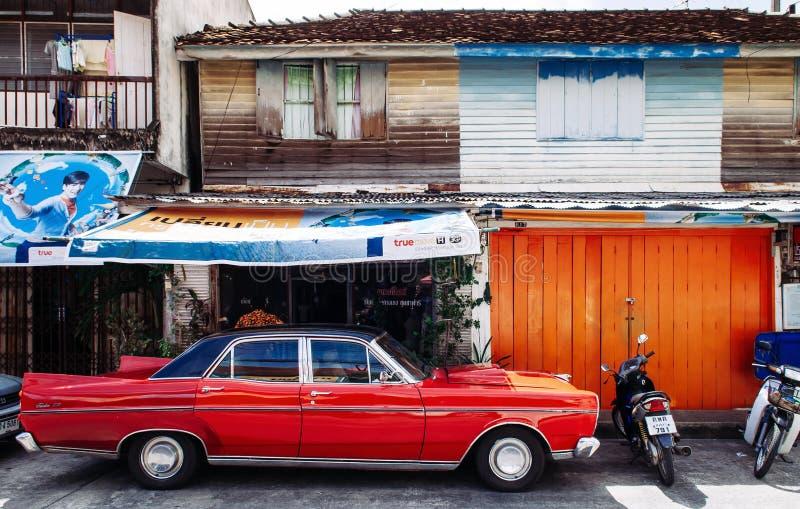 Songkhla, TAHILAND Wibrujący rocznika sportowy samochód i starego miejscowego stylu drewniany dom w Songkhla starym miasteczku -  obrazy royalty free