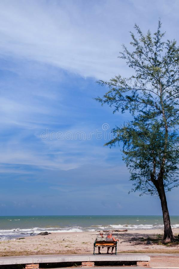 Songkhla, Tailândia - os pares do turista sentam-se no banco na praia famosa de Samila na temporada de verão com o céu azul dispe foto de stock