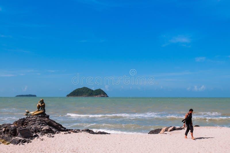 Songkhla, Tailândia - turista que anda perto do ícone de bronze do marco da estátua da sereia da praia de Samila na temporada de  fotografia de stock