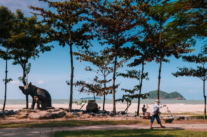 Songkhla, Thailand - local streetfood vender and cat and rat statue at famous Samila Beach in summer season with blue royalty free stock photography