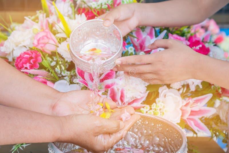 Songkran泰国的节日标志:年轻人的手倾吐水,在更老花 塔玛琳在新年水中庆祝Songkran 库存照片