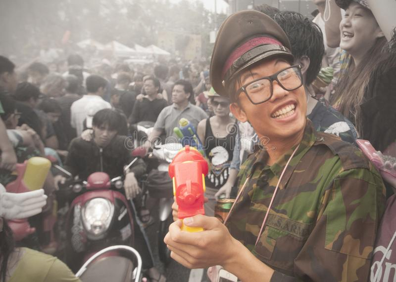 Songkran in Chiang Mai, Thailand. On the 15th of April 2014. A young man in army fatigues smiles at the camera royalty free stock photography