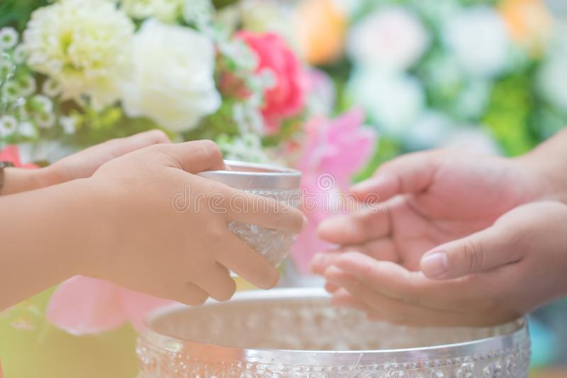 Songkran Thai festival concept : Close-up Pour water on hands of revered elders, gives blessing in Songkran day Thailand with Blur stock photos