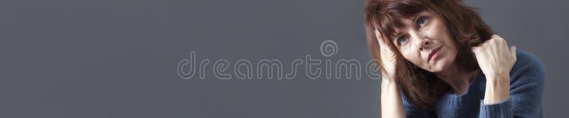 Sonhando acordado a mulher 50s bonita que olha bandeira contemplativa, cinzenta do espaço da cópia foto de stock royalty free