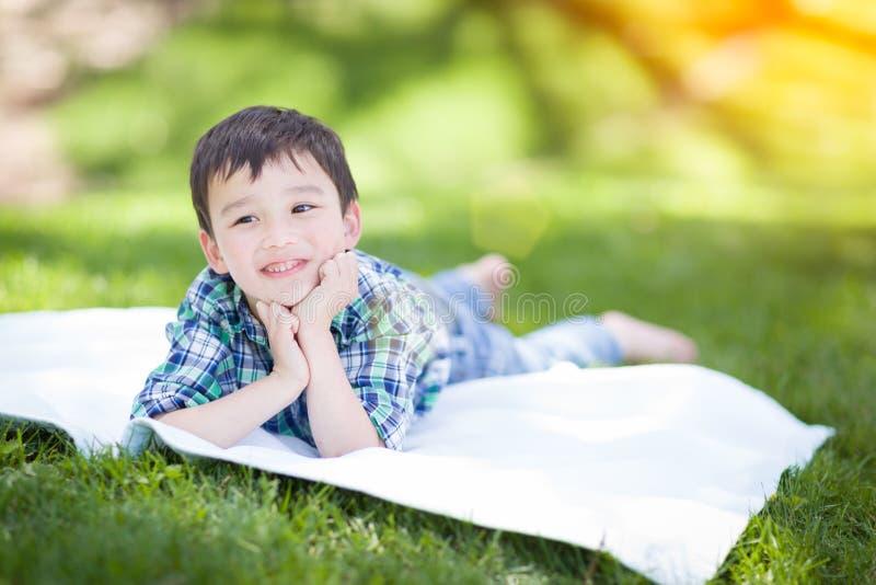 Sonhando acordado raça misturada chinesa e menino novo caucasiano que relaxa fora em T fotos de stock