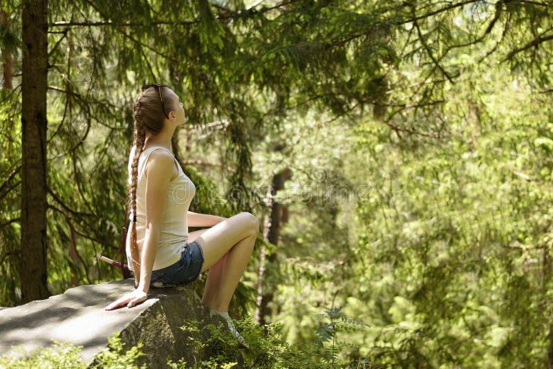 Sonhando a menina bonita que senta-se em uma pedra cercada pela floresta conífera em um dia ensolarado foto de stock royalty free