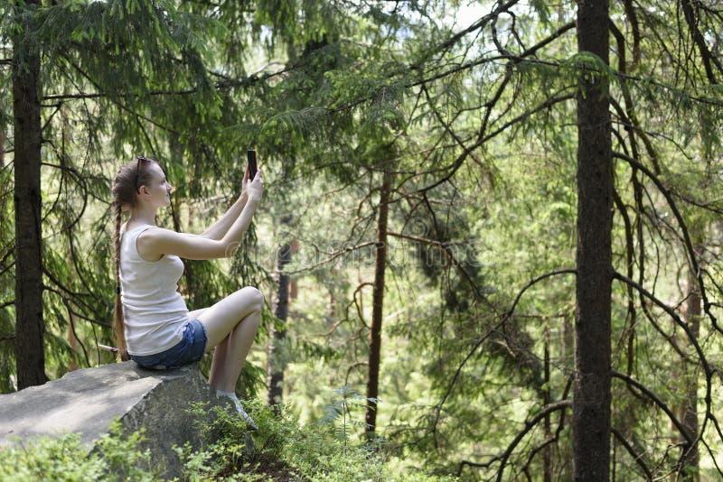 Sonhando a menina bonita que senta-se em uma pedra e que faz o selfie em um smartphone cercado pela floresta conífera em um dia e foto de stock