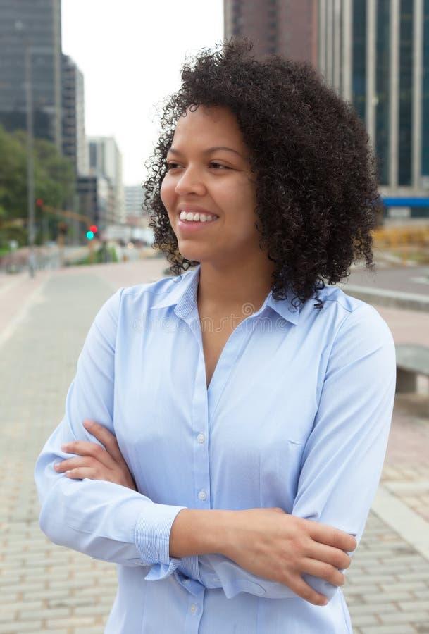 Sonhando a mulher latino-americano na cidade com braços cruzados imagens de stock
