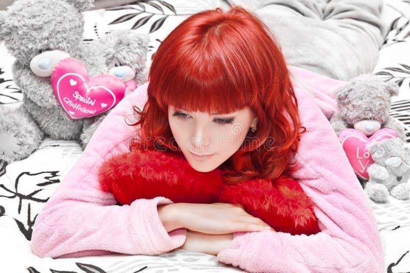 Sonhando a mulher nova na cama com os brinquedos que olham para baixo foto de stock royalty free