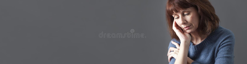 Sonhando a mulher 50s bonita que olha bandeira contemplativa, cinzenta fotografia de stock