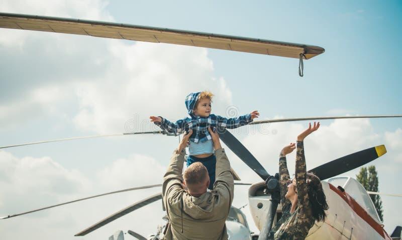 Sonhando o conceito Criança pequena que sonha sobre o voo no céu no plano Filho pequeno que sonha de ser piloto nos pais imagem de stock