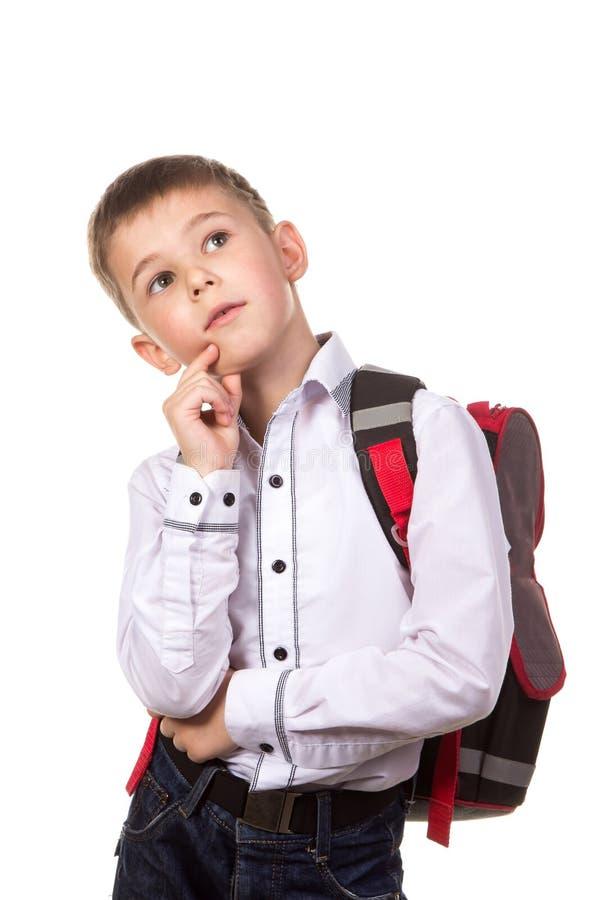 Sonhando o menino de escola que está no fundo branco em uma pose pensativa fotos de stock