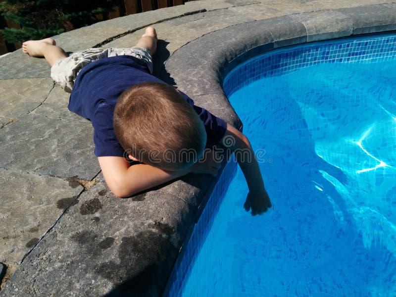 Sonhar acordado da piscina do menino imagem de stock