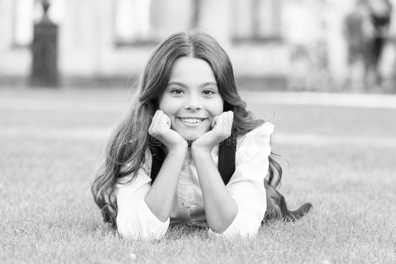 Sonhar com o futuro Garota feliz relaxa com grama verde Pequena criança com sorriso fofo Geração futura Futuro da educação imagem de stock royalty free
