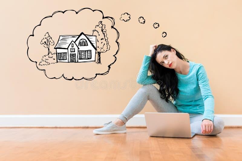 Sonho da casa nova com a mulher que usa um portátil imagens de stock royalty free