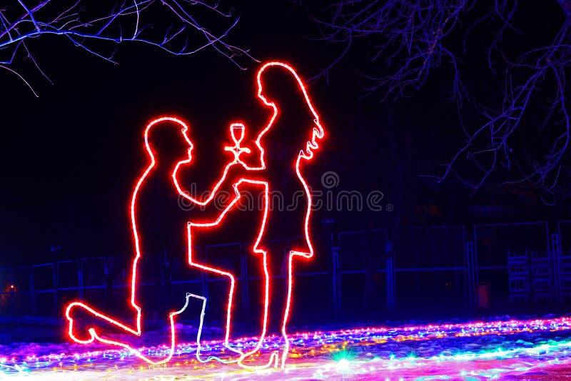 Sonho romântico sobre as mãos e corações de oferecimento de um homem em seus joelhos imagem de stock