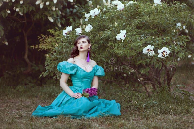Sonhos da mulher do assento sob um arbusto imagens de stock